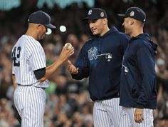 New York Yankees relief pitcher Mariano Rivera, left, hands the ball to Andy Pettitte as Derek Jeter