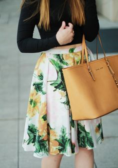 Black cropped top, white skirt with light orange and green tropical print midi skirt, and tan handbag