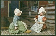 Twee kleine meisjes in dracht zittend op straat. 1910-1920  #NoordHolland #Volendam