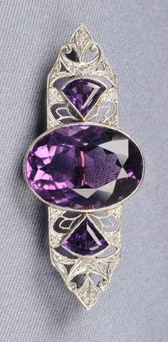 An Art Deco platinum topped 14k gold, amethyst and diamond brooch. Bezel-set with an oval-cut amethyst flanked by fancy-cut amethysts, foliate engraved platinum-topped 14kt gold mount, length 2 in.