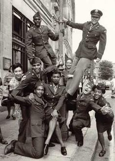 Happy group of WWII vets celebrate the end of the war in Europe.  My note - Great pic! I've never seen female black military during WWII!: