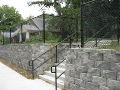 simple grey stones for retaining wall design under black metal fence near - Designing Retaining Walls