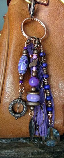 This handmade tassel charm can be used on your purse, backpack, zipper, wherever youd like to add some charm! Its made up of antiqued copper chain and charms, a beautiful leaded glass cube, and a gorgeous variety of beads - ceramic, glass, stone, and wood. The suede tassel is a rich purple color. It is approximately 6.5 long.