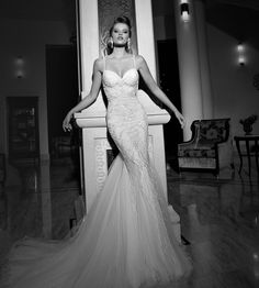 #GaliaLahav -- Nikita is a Charleston inspired dress with botanical motifs and embroidery. From the waist to the floor is a floral lace embroidery that gradually transforms into a feather pattern as it reaches the floor. It has a tulle train and pearl beaded trims lining the low sheer back. The straps are thin lined in decorative pearl beading.