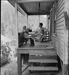 "Bill Daniels, a miner, and his two daughters on the front porch of their three room house for which they pay $7 monthly. There is no running water in the house; the privy is used by ""four or five"" families and is in bad condition. Mr. Daniels has about forty chickens and a large garden. Panther Red Ash Coal Corporation, Douglas Mine, Panther, McDowell County, West Virginia., 08/26/1946"