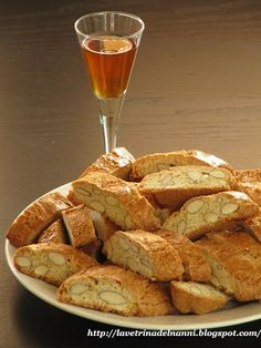 Cantucci e vin santo~ Cantucci, the famous almond biscotti of Tuscany are brought to the table at the end of a meal, with a bottle of Vin Santo, a sweet, local, dessert wine.