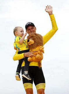 Chris Froome of Great Britain and Team Sky with his son Kellan on the podium after winning the yellow jersey during stage twenty one of Le Tour de...