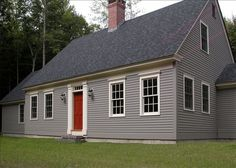 Classic New England cape code style with solid wood front door with transom and 6 over six windows