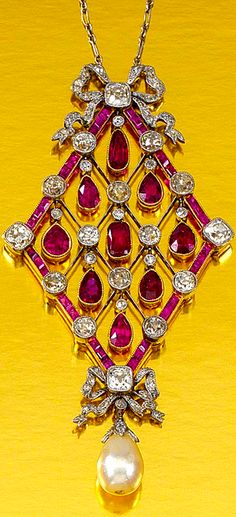 RUBY, PEARL AND DIAMOND PENDANT NECKLACE, CIRCA 1910. The open work lozenge-shaped pendant designed as a knife-edge lattice millegrain-set with circular-, single-cut and cushion-shaped diamonds and articulated pear-shaped rubies, suspending a diamond capped pearl drop, embellished by two tied ribbon motifs highlighted by rose- and single-cut diamonds, to a fine curb and fetter link chain, length approximately 464mm.