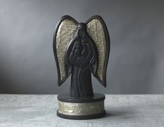 """Holy Family and Angel Nativity.  surrounding the base of the sculpture , Rejoice!  Emmanuel has come to thee! Each is hand-carved  with its own individual and one-of-a-kind  markings. Measures 13 1/2"""" H × 6 5/8"""" in diameter."""