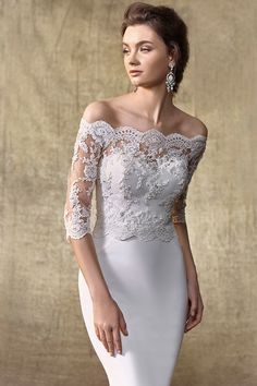 <strong class='info-row'>Enzoani</strong> <div class='info-row description'>Style Jacket X   Channel the glamour of Old Hollywood screen sirens and bridal royalty with this beaded corded lace and tulle jacket featuring an off-the-shoulder neckline that is both contemporary and timeless. Complete with elegant 3/4-length sleeves and a back closure of delicate crystal buttons.</div> <div class='row info-row text-center'> <div class='col-xs-6 col-xs-offset-3'> <a…