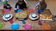 Presentatie van het eten en tafeldekken, kinderen helpen mee.