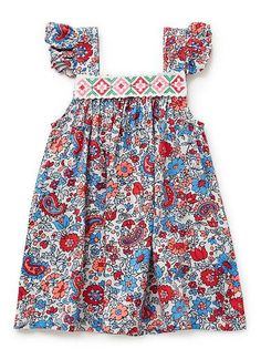 100% Viscose dress. Smock dress with all-over paisley print. Features cross stitch panel on front neckline, and ruffles on straps. Available in colour shown.
