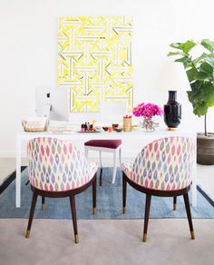 Home office space with a white desk, colorful printed armchairs, and bright modern art