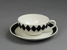 'Svart Ruter' (Black diamond) cup and saucer of high-fired earthenware, part of a tableware range, with painted decoration in black, designed by Karin Björquist ca. 1955, made by Gustavsberg, Sweden, ca. 1955-1956.