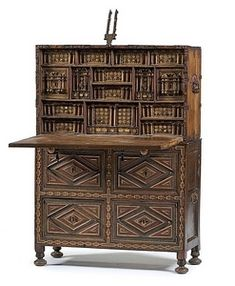 A Spanish vargueno chest, 16th century with cabinet base. The chest decorated with elaborate iron hardware over red velvet. [The fall-front]falls forward and rests on two pull out supports with carved shell knobs.