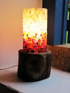 Luminárias cilíndricas com base em madeira (acácia). Superfície musiva realizada em técnica direta, utilizando pedras naturais e semipreciosas. Estrutura realizada em madeira e acrílico, com iluminação interna do tipo LED para não gerar aquecimento e proporcionar um menor consumo energético.