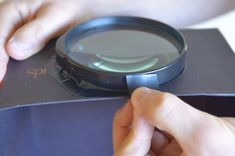 Step 1 of DIY photo projector project.  Cut hole in shoebox and tape in magnifying glass
