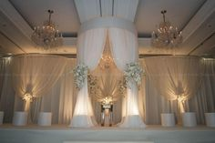 The curtains will be tied back with large sprays of white hydrangeas, white phalaenopsis orchids, blush roses, ivory spray roses, and white sweet peas.
