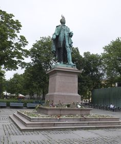 """""""Grief in the public domain"""". Brynjulf Bergslien statue of Henrik Wergeland on Eidsvolls space is decorated with flowers."""