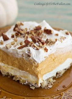 Luscious and fluffy pumpkin lasagna is the perfect dessert to serve friends this fall. This dessert is layered between a buttery pecan crust, sweetened cream cheese and whipped cream layer and topped with more pecans.