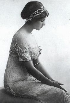 """""""The actress Gladys Cooper, later to be the star of stage and screen in The Second Mrs Tanquery and My Fair Lady, wears a high-waisted Empire line evening dress in the new fluid, classical style. Although the fussy frills have gone, the surface of the dress is still intricately beaded. Feathers, tiaras and jewelled bands were often worn in the hair for the evening."""""""
