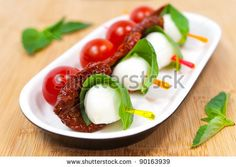 stock photo : Canapes with cherry tomato, mozzarella cheese, dried tomatoes and basil