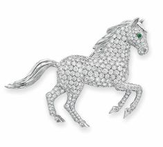 A DIAMOND AND EMERALD HORSE BROOCH, BY CARTIER  Designed as a circular-cut diamond horse, with circular-cut emerald eyes, mounted in 18k white gold, with French assay marks (partially indistinct) and maker's mark Signed Cartier, 849950