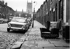 Radcliffe, Thomas Street 1965  Looking up Thomas Street, Radcliffe, off Deansgate, with the St Thomas's Church tower, looming on the misty skyline. This 1965 picture showing a second-hand furniture shop displaying its goods alongside the cobbled street.