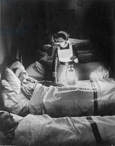 A nurse holding a lamp as she visits patients on a ward at Westminster Hospital, December 1940 (b/w photograph) - © Mirrorpix / Bridgeman Images