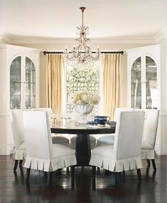 round table for dining & double as an entry area (w/ chairs pulled away); corner cabinets for china & glassware & bookcases so the room could triple as a library; slipcovers for easy care & decor change  --  photo Traditional Home