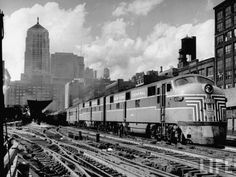 """marmarinou: """" New York Central passenger train with a streamlined locomotive leaving La Salle Street station, with city skyline in the background. Location:Chicago, IL, US Date taken:July 1948 Photographer:Andreas Feininger Life Magazine """""""