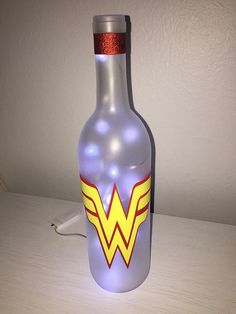 Wonder Woman lighted wine bottle  Materials used are Frosted spray paint, vinyl, acrylic seal, rubber grommet, and ribbon. Comes with 20 Mini micro green LED lights that includes CR2032 batteries. Batteries supply over 24hrs of electric light and more with breaks.