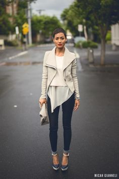 Shop this look on Lookastic:  http://lookastic.com/women/looks/cropped-sweater-and-biker-jacket-and-tunic-and-skinny-jeans-and-heels-and-clutch/2328  — White Cropped Sweater  — Grey Leather Biker Jacket  — White Chiffon Tunic  — Navy Skinny Jeans  — Navy Leather Pumps  — Grey Leather Clutch