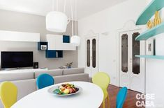 Renovated three-room apartment: 88 m2 with a young touch and curved lines -...- Trilocale rinnovato: 88 mq con tocco giovane e linee curve – Cose di Casa  living room, dining area, white table, yellow and blue chairs, white pendant lamps, colored shelves, sofa, TV area, white lacquered wall units, antique wooden and decorated glass doors  -#clearglasstables #glasstablesdrawing #glasstablesrestaurant #glasstablessketch #glasstablesstand #stainedglasstables #tallglasstables #woodenglasstables Dining Area, Dining Table, Curved Lines, Teak, Stained Glass, Shelves, Living Room, Furniture, Glass Tables