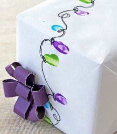 Kids fingertips in paint to make Christmas lights design gift wrap.