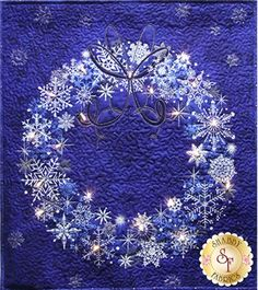 Starry Night Christmas Wreath Kit in Blue: If you've been looking for a holiday project that is quick, easy, and spectacular - this is it!! The Christmas Wreath Wallhanging features a wreath panel with real lights! Kit includes basic instructions, front panel, binding, backing, and strand of 20 white lights. Requires 3 AA batteries (not included). Fabrics feature metallic gold accents. Finishes to approximately 23