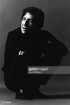 Canadian poet novelist and composermusician Leonard Cohen dressed in black squatting with arms crossed over knees