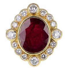 Oval Ruby  Diamond  Cluster Ring | From a unique collection of vintage cocktail rings at https://www.1stdibs.com/jewelry/rings/cocktail-rings/