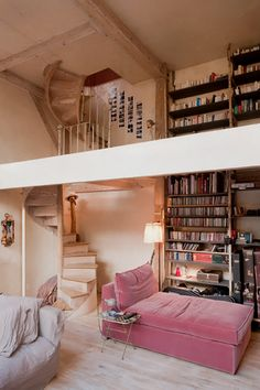 I am in love with this Paris home: cast-iron bookshelves from the 1900s, open mezzanine connected to the living area by a spiral staircase, and a rosy chaise #bookshelves #home_library