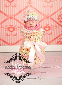 Newborn baby girl in candy hearts vase wearing rainbow colored beanie in front of pink heart damask backdrop. Valentine's Day Backdrop  www.TheAthensNewbornPhotographer.com