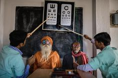 """Eye-care workers use test-lens frames to conduct eye exams in India's Sundarbans region. Their goal: to help reduce India's blind population of more than eight million.  This photo was originally published in """"Why There's New Hope About Ending Blindness,"""" in September 2016.  PHOTOGRAPH BY BRENT STIRTON 
