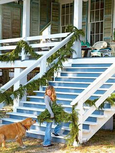 The iconic blue-and-white staircases of homes that line Mobile Bay in Southern Alabama bear simple green garland to bring in the holiday spirit.