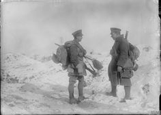 Two British soldiers carrying their rifles and equipment photographed in the snow at La Boisselle, December 1916.© IWM (Q 1708).