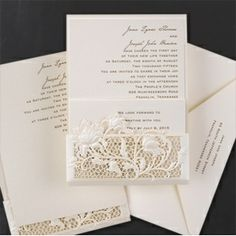A delicate latte shimmer pocket, with an intricate floral die-cut at the bottom, holds a matching latte shimmer invitation and enclosure cards.