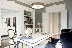 Margaret Bosbyshell of Margaux Interiors Ltd., in Atlanta. Hollywood Regency meets Southern Traditional. Millwork, door frames, and double   doors are killing me in this room and the sitting room beyond. Love the white, black, and shiny mossy-grey color palette with accents of gold and velvet.  (Source: houseparts)
