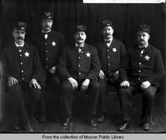 """Night Policemen""  ca.1904 -  Muscatine night policemen all in uniform. All of the men are wearing their hats and badges. The man to the left has the number 3 on his hat, the man next to him has a number 2. The man in the center has the letters NC on his hat. The next man (second from the right) has the number 6. The man on the far right's hat is unidentifiable. Muscatine County, Iowa"