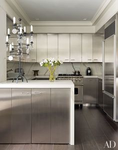 The kitchen of designer David Kleinberg's Manhattan apartment features stainless-steel cabinets offset by Calacatta gold marble counters.