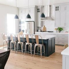 Kitchen w/ Dark Grey Island & Stools and White Cabinets w/ Hardwood Floor | House of Jade Interiors