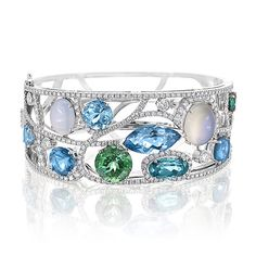 Boodles. BRACELETS. Dragonfly. Inspired by the gossamer fine wings of a dragonfly this bracelet is constructed of fine paths of twinkling diamonds, like the skeleton of the wings set with sparkling stones recreating the iridescence of the insect's colouring in the sunlight. Featuring marquise cut aquamarines, cabochon sapphires with magical moonstones.
